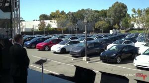 Tesla holds shareholder meeting in front of crowd of people in Teslas